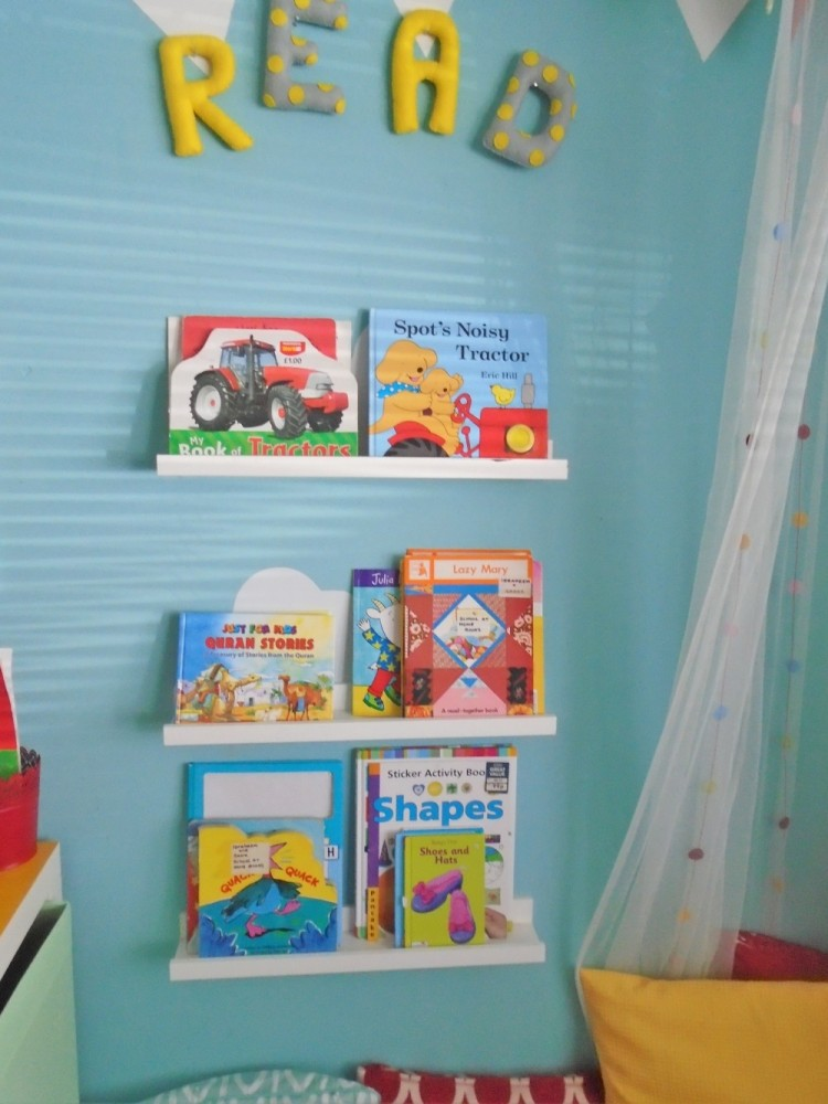 After image of a reading nook with white shelves, blue walls and children's books