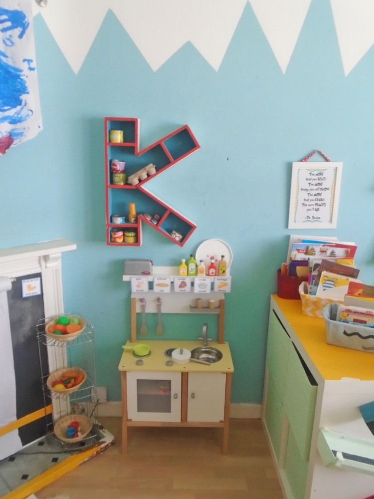 Play kitchen area in the Dr Seuss Play Room. A wooden letter K shelf hangs above the kitchen set.