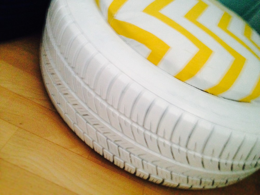 Close up image of an upcycled, painted tyre with seat cushion