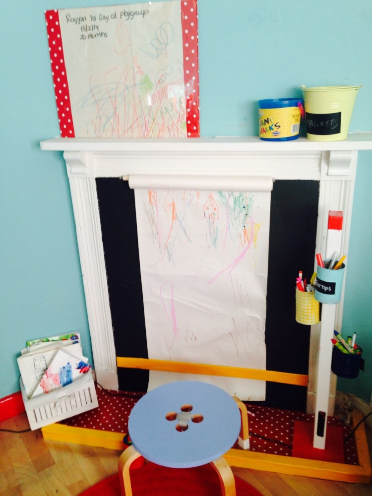 A roll of Ikea art paper hanging from the mantel in the art corner