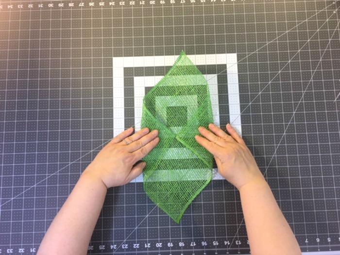 Daisy wreath tutorial step two: Fold the corner of your poly burlap / Grillo Designs www.grillo-designs.com