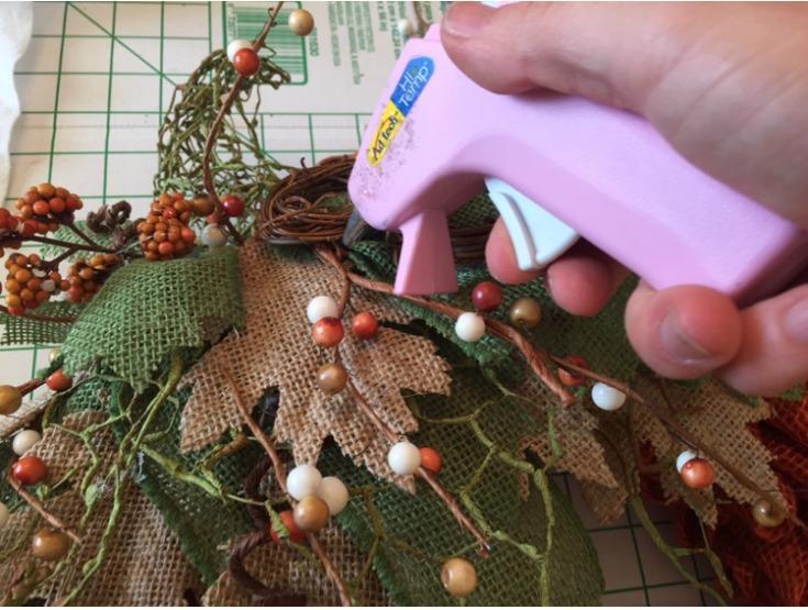 Use a hot glue gun to attach fall embellishments to your burlap pumpkin wreath / Grillo Designs www.grillo-designs.com