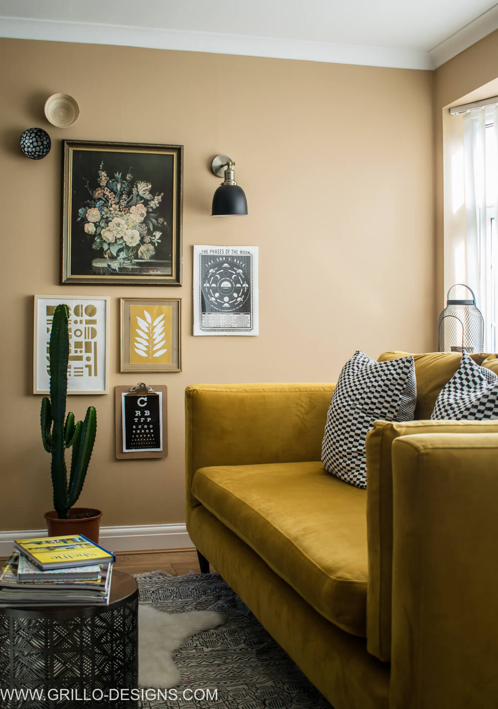Yellow velvet sofa next to a vintage modern gallery wall / grillo designs