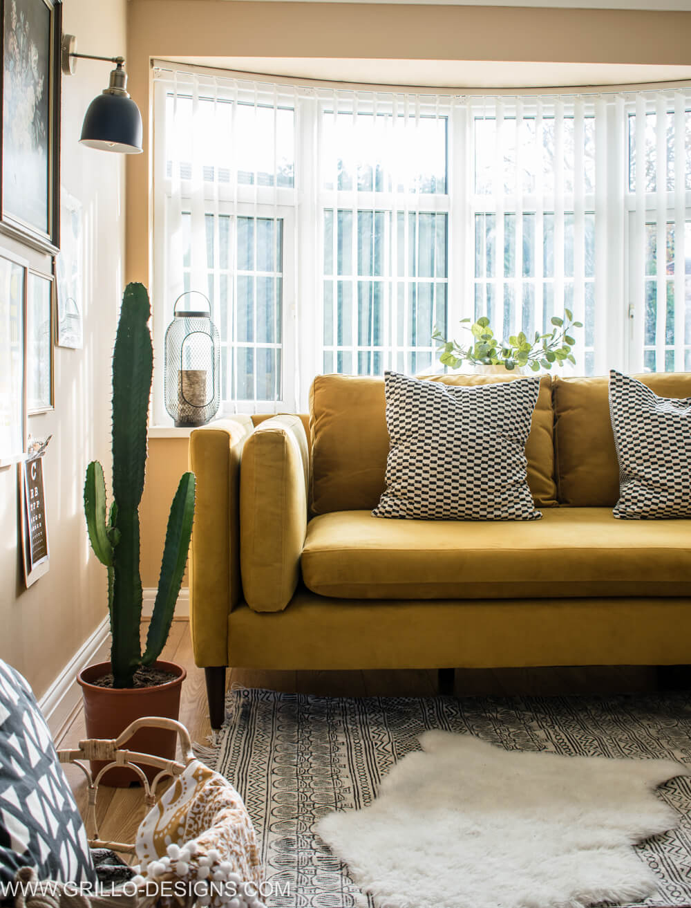Velvet mustard sofa in front of a large bay window