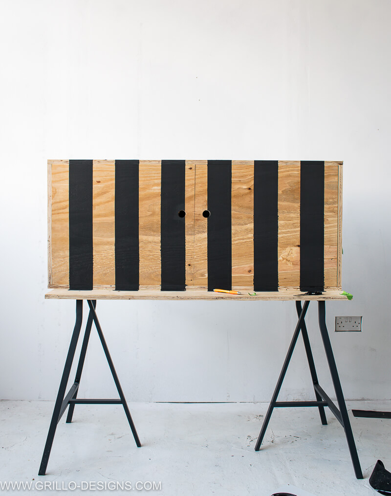 DIY tv stand painted with black stripes. Easy tutorial to follow tutorial with plans How to builsd a Diy tv stand with doors #diytvstand #tvstandideas #tvstandideasforlivingroom #grillodesigns