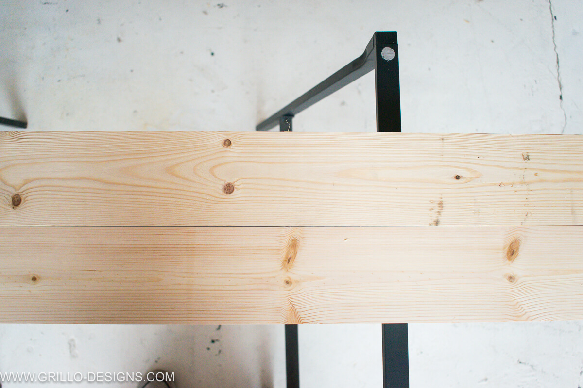 Place the two pieces of wood planks together to create the table top of the overbed table
