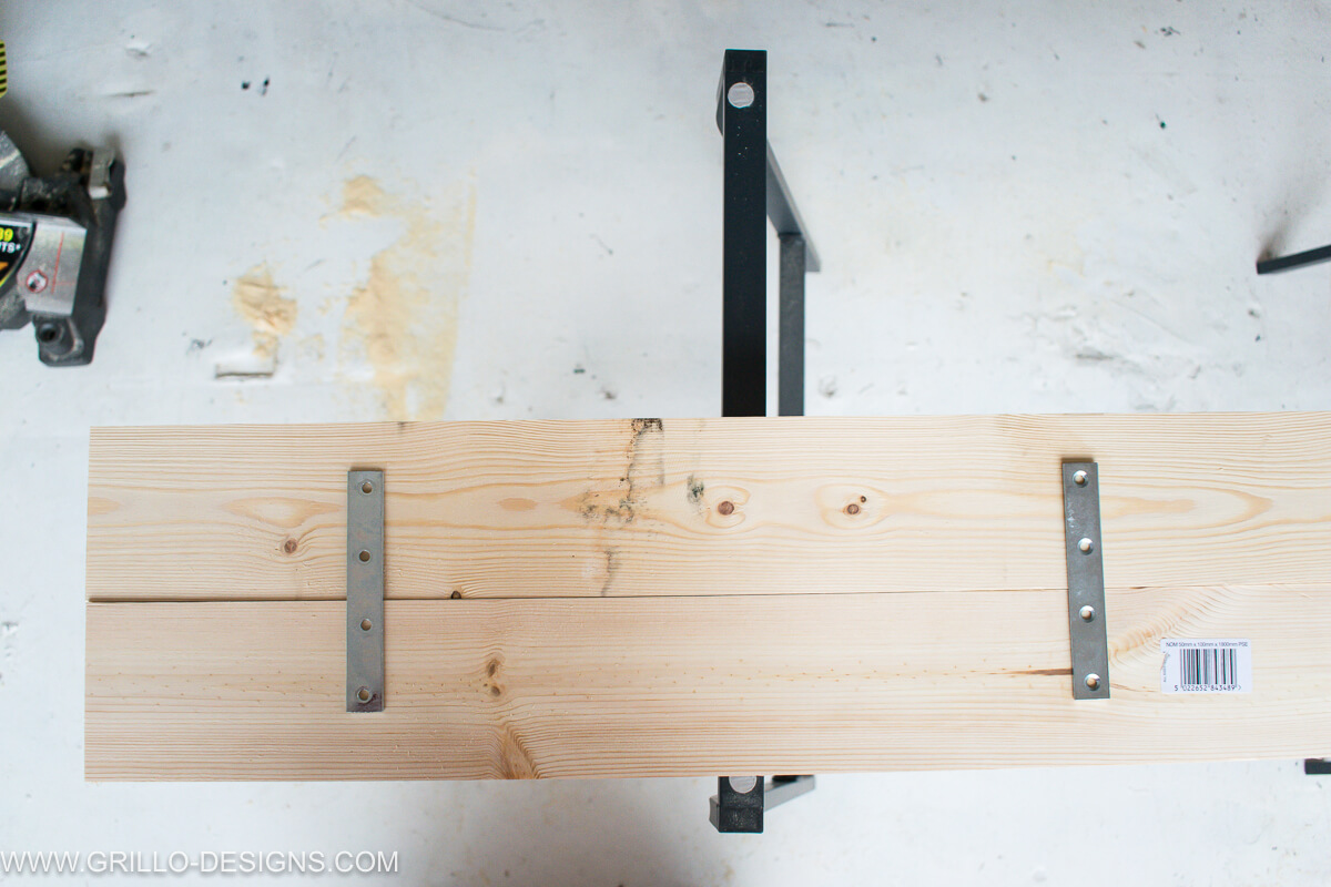 Place the straight brackets evenly across the table top of the overbed table