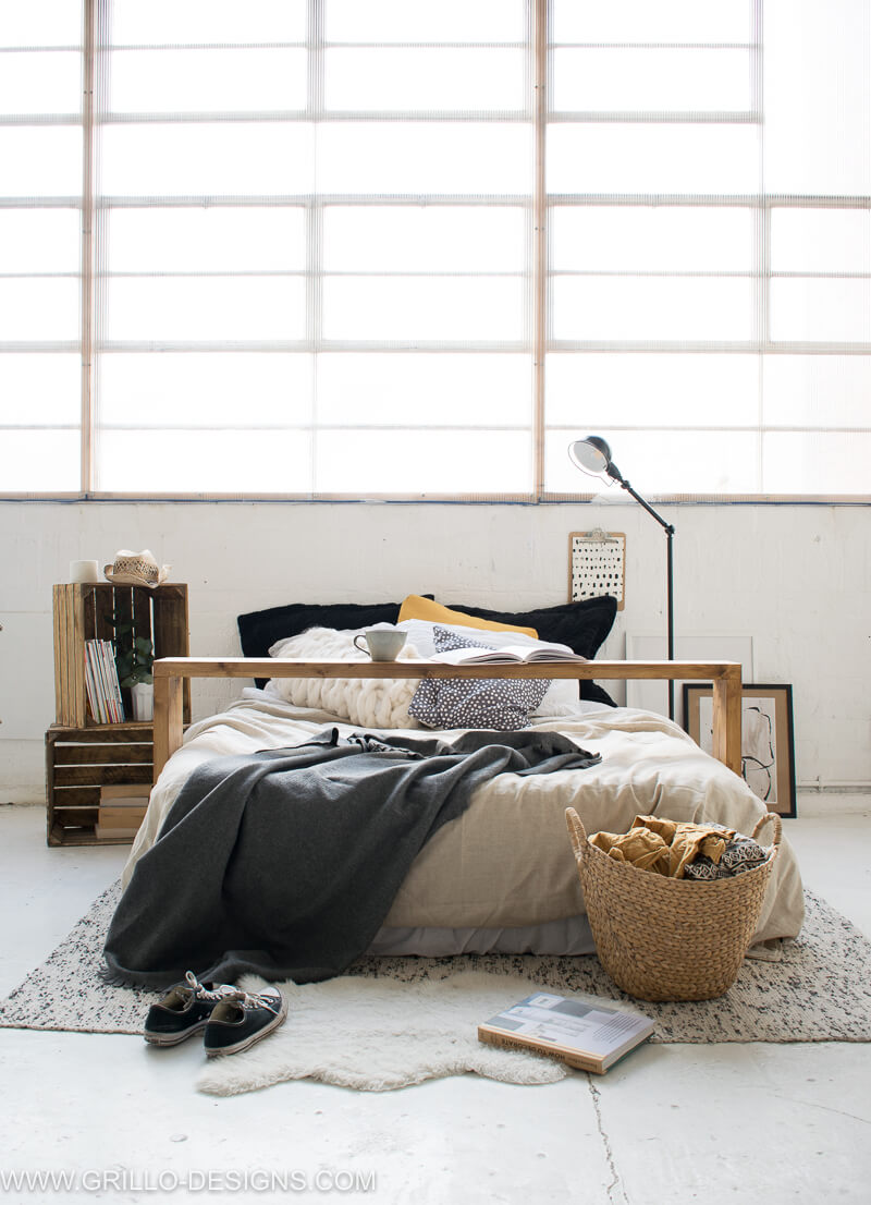 The overbed table styled in an industrial bedroom setting under large windows