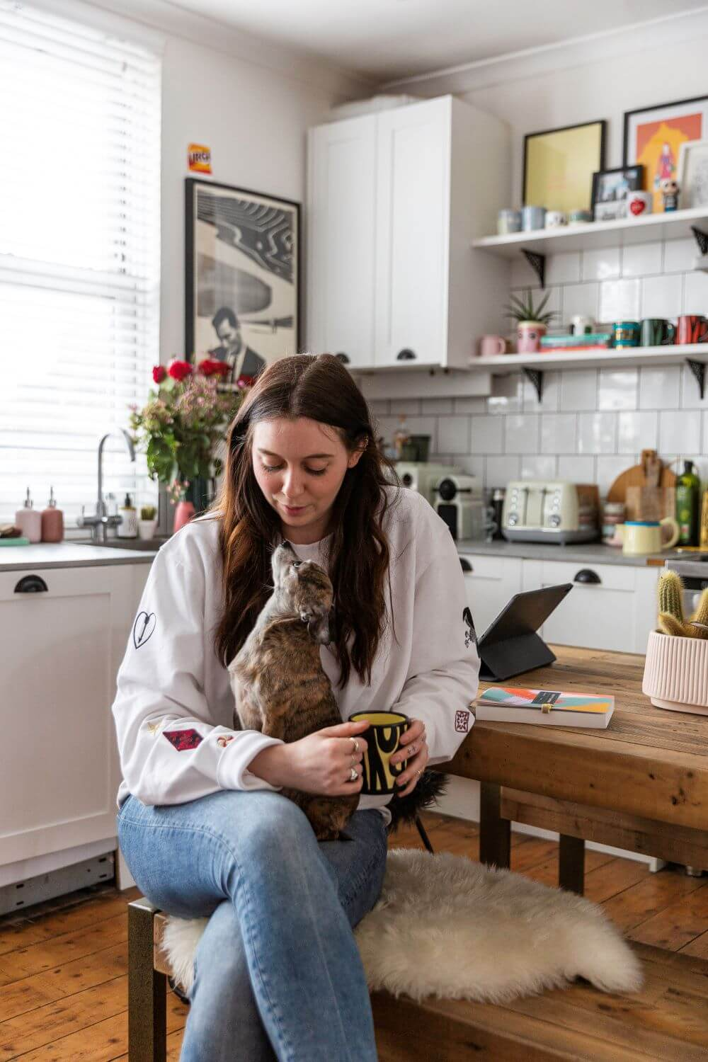 Emma jane palin sitting on a dining bench with her dog george for this colourful rental home tour