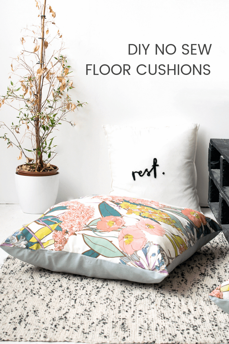 Large floor cushion on a black and white rug, next to a dead plant