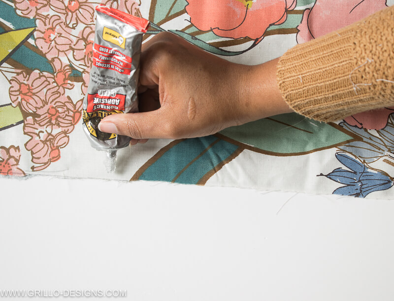 Photo of my hand applying the glue to the correct side of the fabric to make the diy large cushions