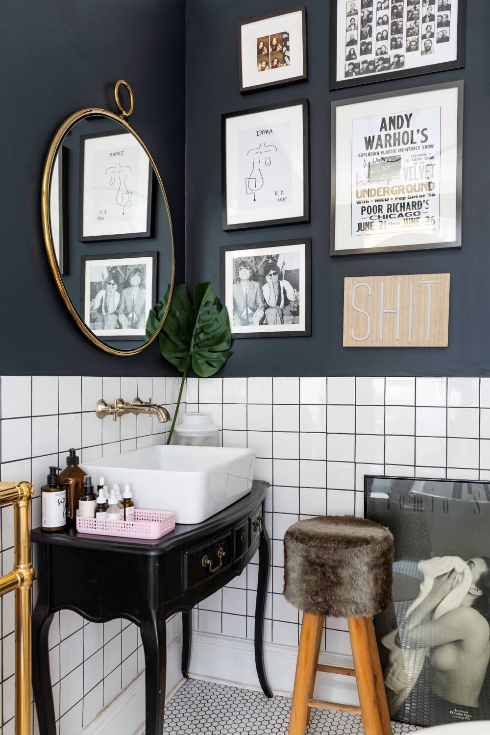 A colourful rental :bathroom with dark tiled grout and black painted walls