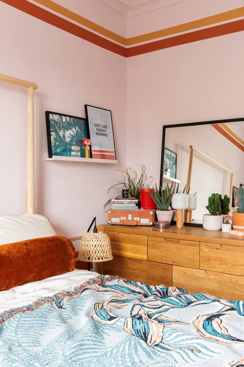 A colourful rental: A corner view of a bed and dresser with art, mirrors and plants