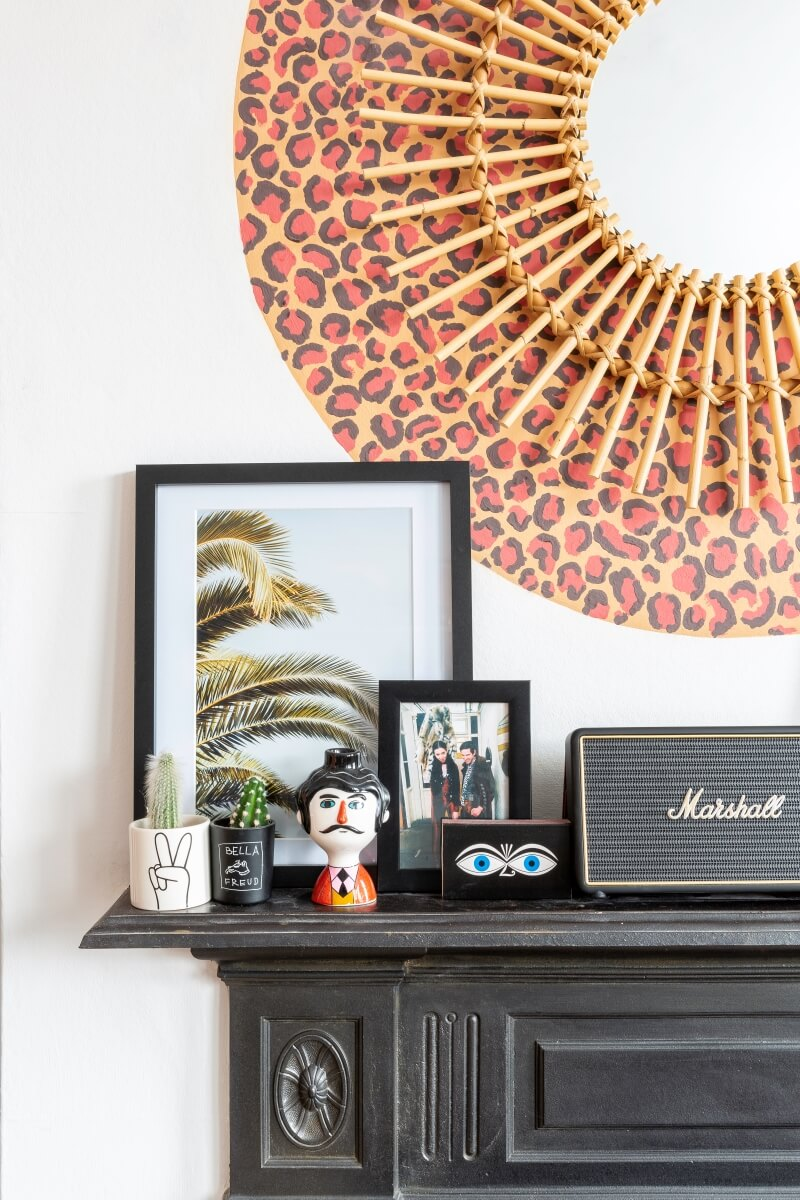 A colourful rental: leopard print behind mirror above black fireplace