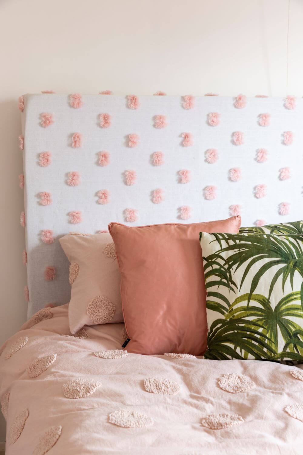 Decorate with Pink Home tour: Close up of diy headboard with pink and botanical cushions