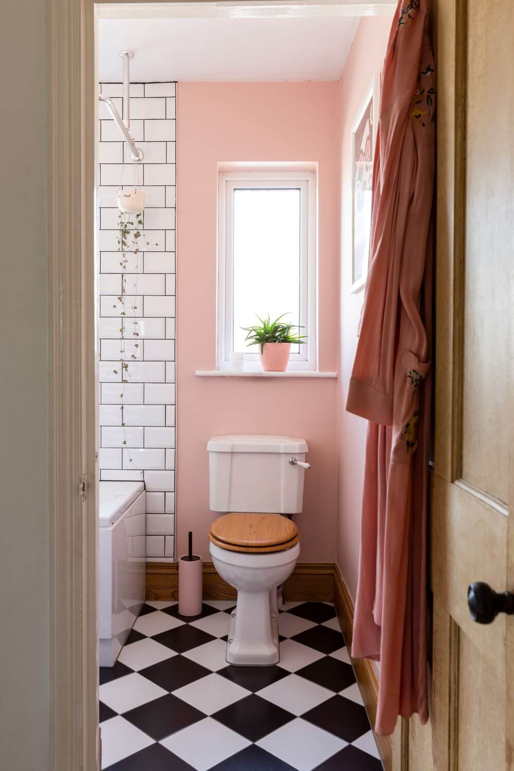 Decorate with Pink Home tour: Bathroom painted pink with black and white checked floor.