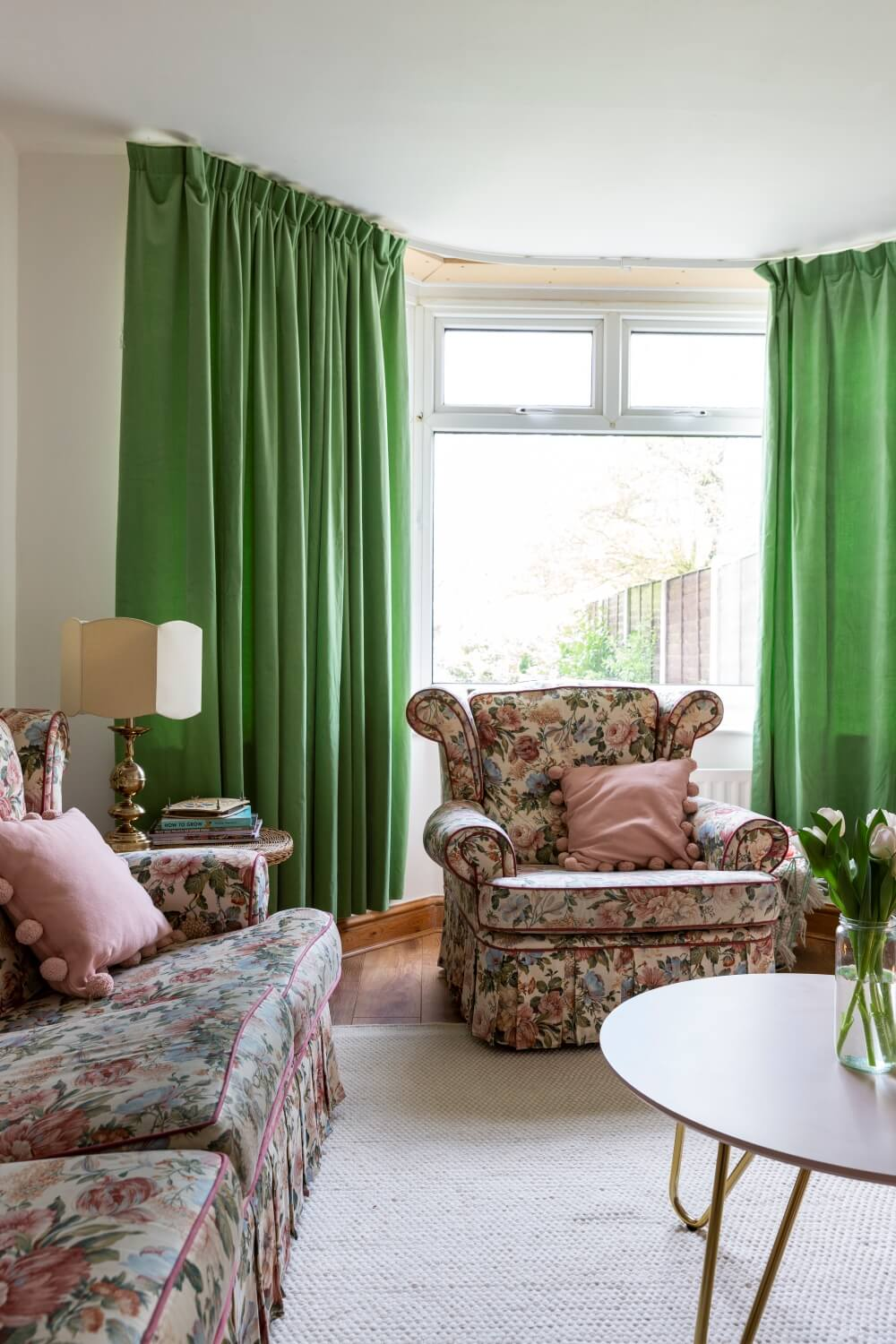 Decorate with Pink Home tour: floral vintage sofa arm chair in front of large bay window framed with lined green curtains.