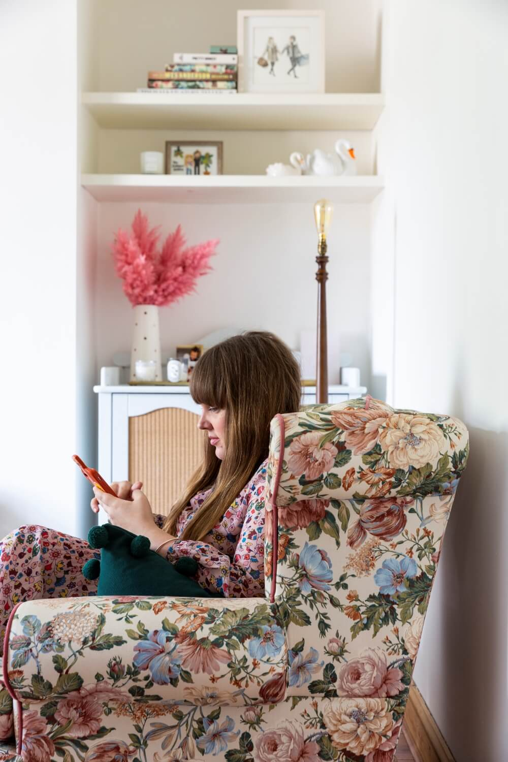 Decorate with Pink Home tour: Charlotte jacklin sitting in vintage floral sofa looking at her phone