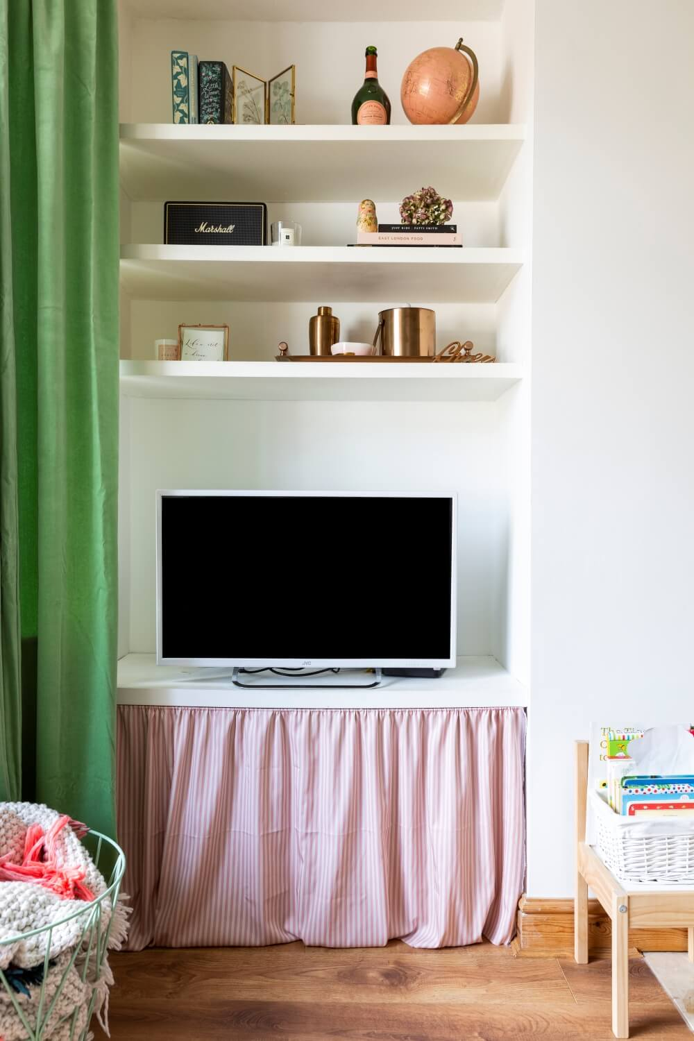 Decorate with Pink Home tour: View of a styled shelf alcove with diy curtain skirt below TV to hide ugly wires.