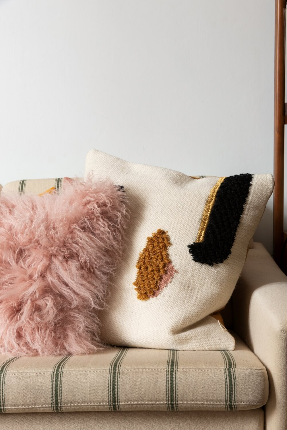 Close up of pillows on striped vintage sofa