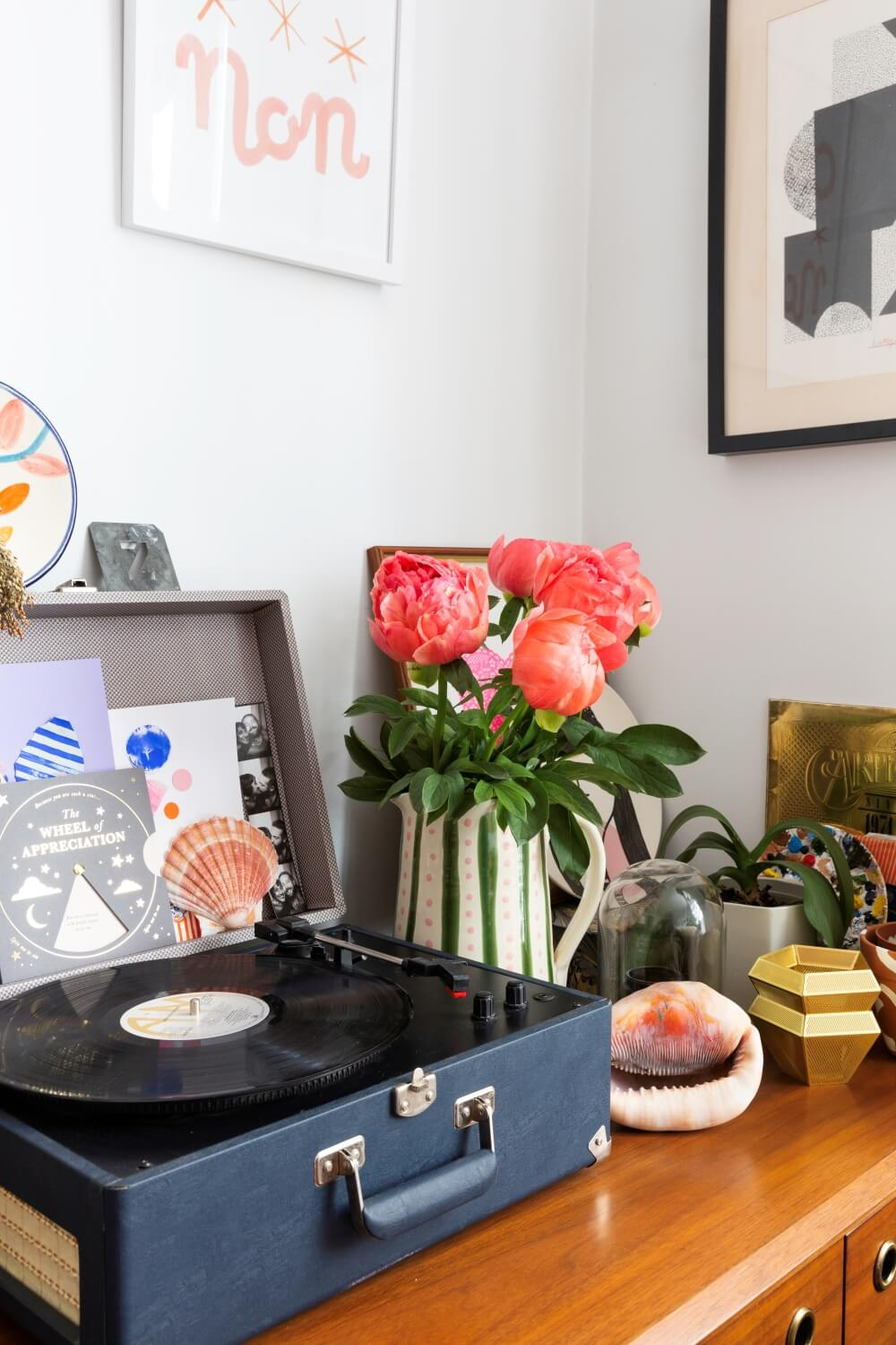 record player on west elm dresser next to vase of peonies