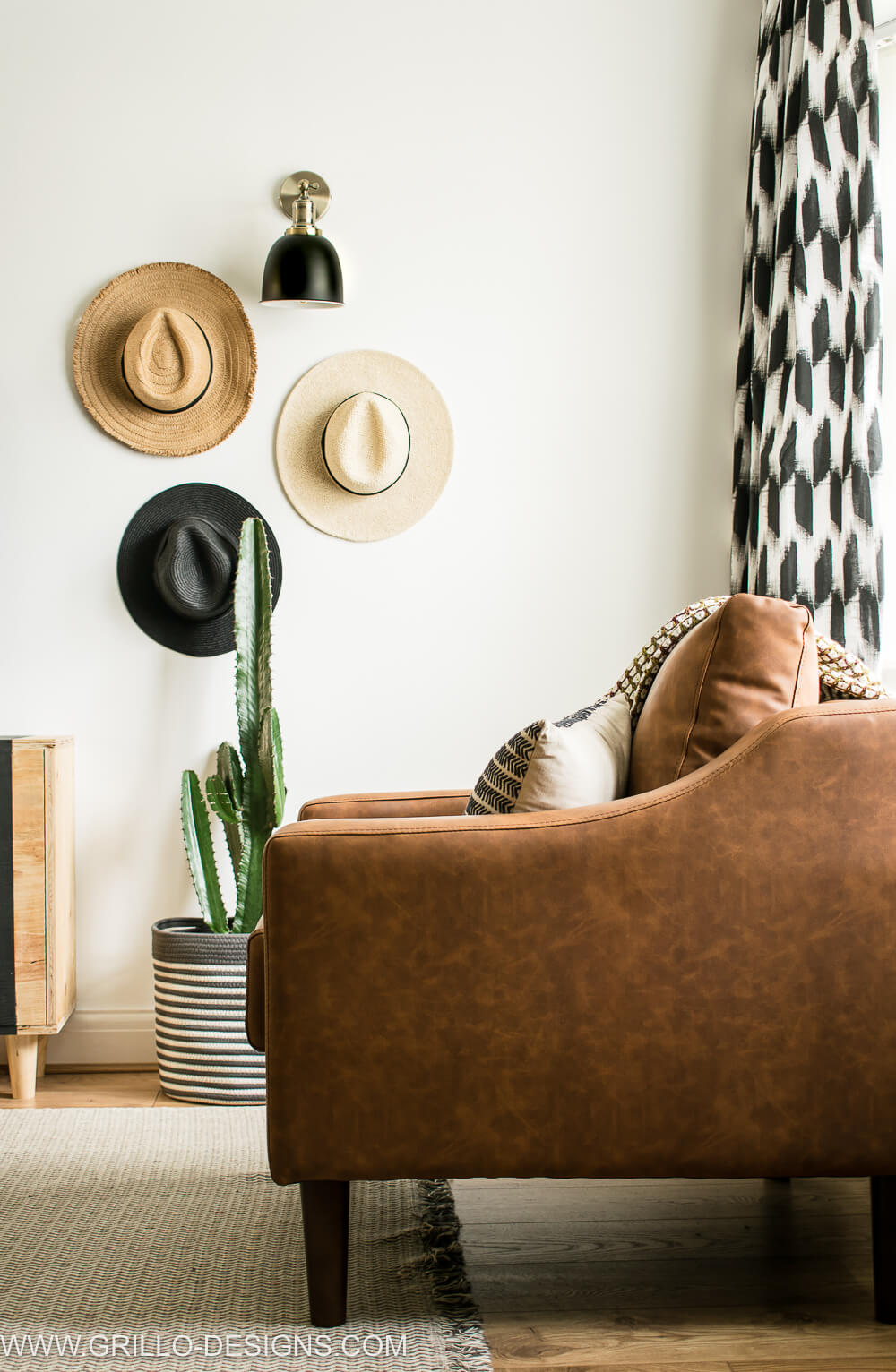 Faux leather sofa with gallery hat wall in the background
