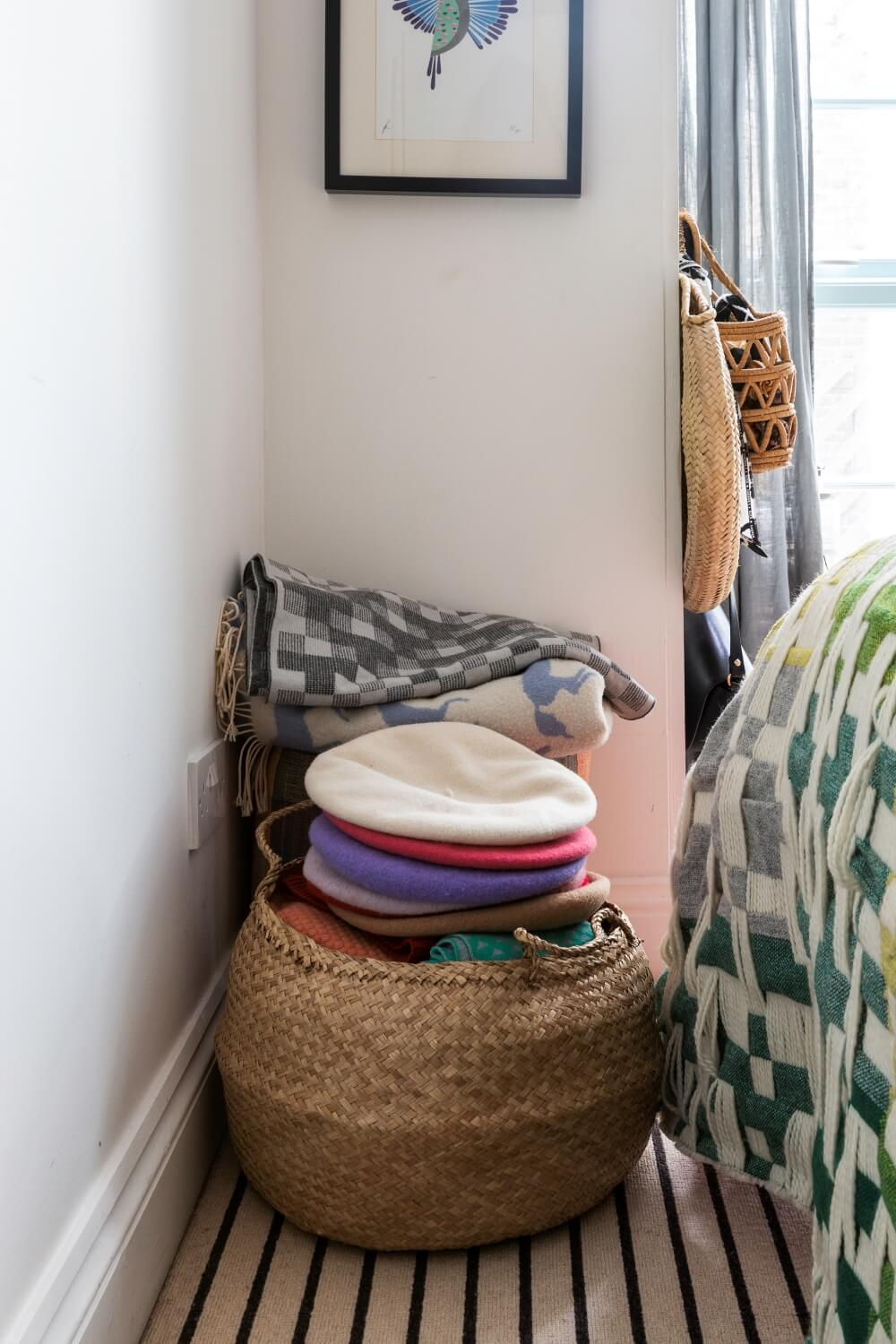 Small basket of hats next to the end of the bed for additional storage