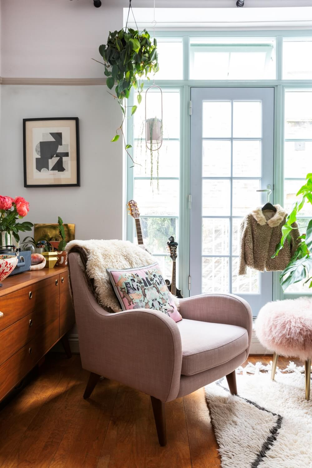 pink arm chair in front of large pale blue windows in listed property. Indoor plants suspended from curtain rails