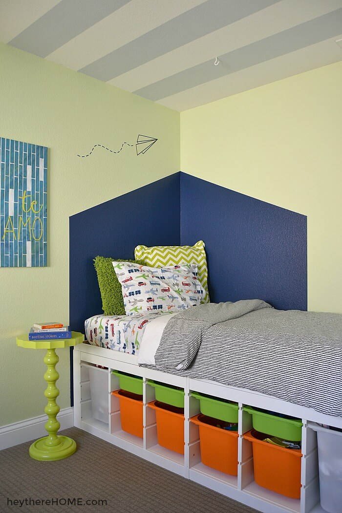 diy platform bed using trofast units to elevate mattress in a boys bedroom. The trofast unit contains green and orange bins.