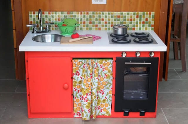 mini play kitchen using the frame of the trofast unit. the kitchen is painted red and has a min curtain and a small sink