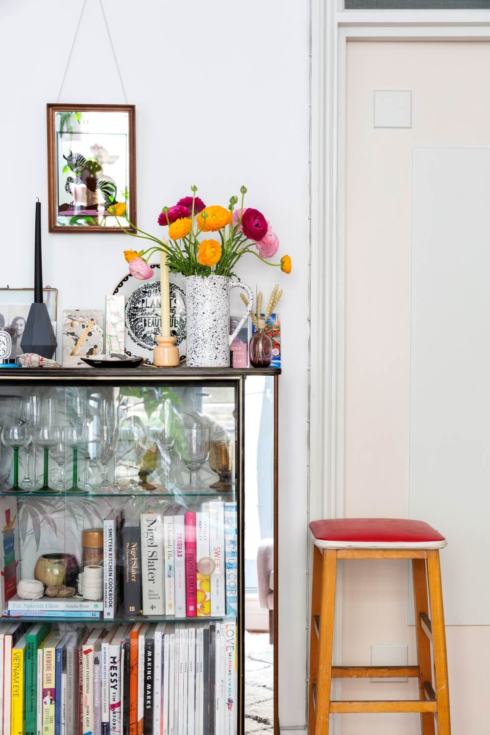 Glass vintage sideboard filled with books and other ornaments.