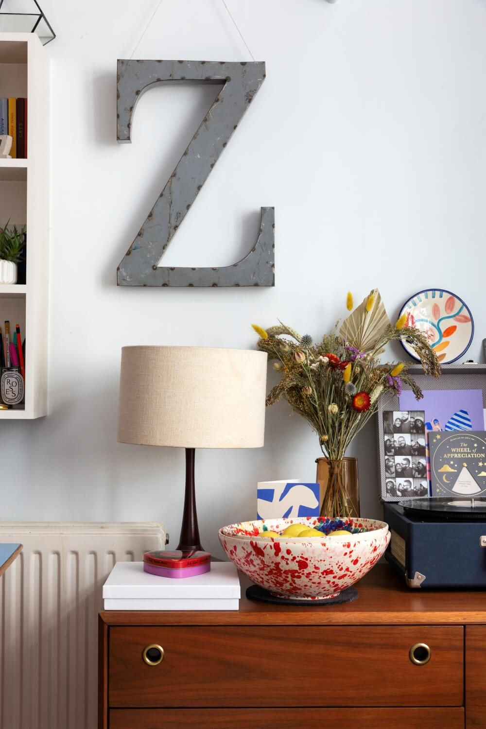 large industrial style Z letter hanging from picture hooks. Z is hanging just above midentury dresser