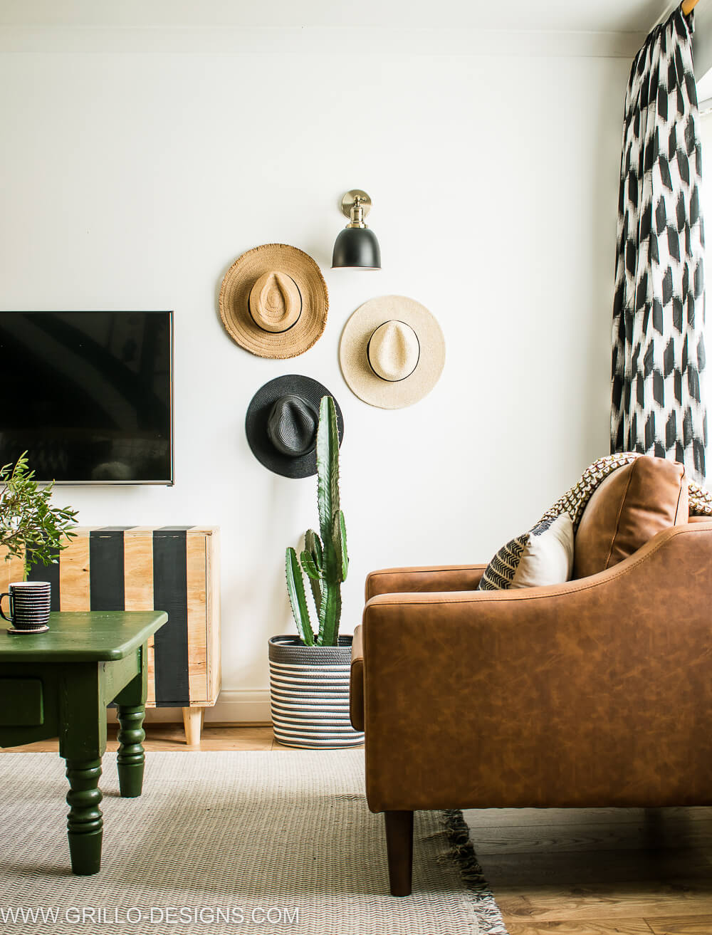Brown sofa with cactus and gallery hat wall in the background