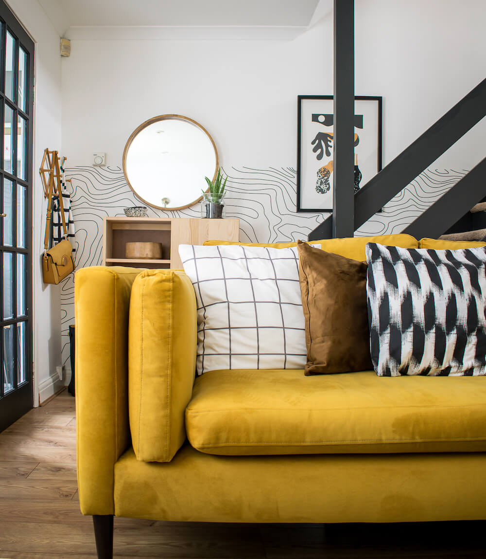 DIY monochrome cushions on yellow sofa with stairs in background