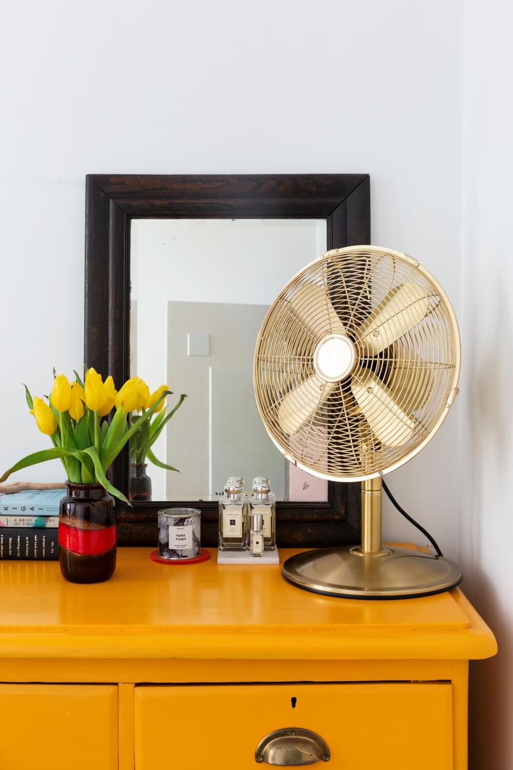 Vintage gold fan on top of the yellow painted chest of drawers