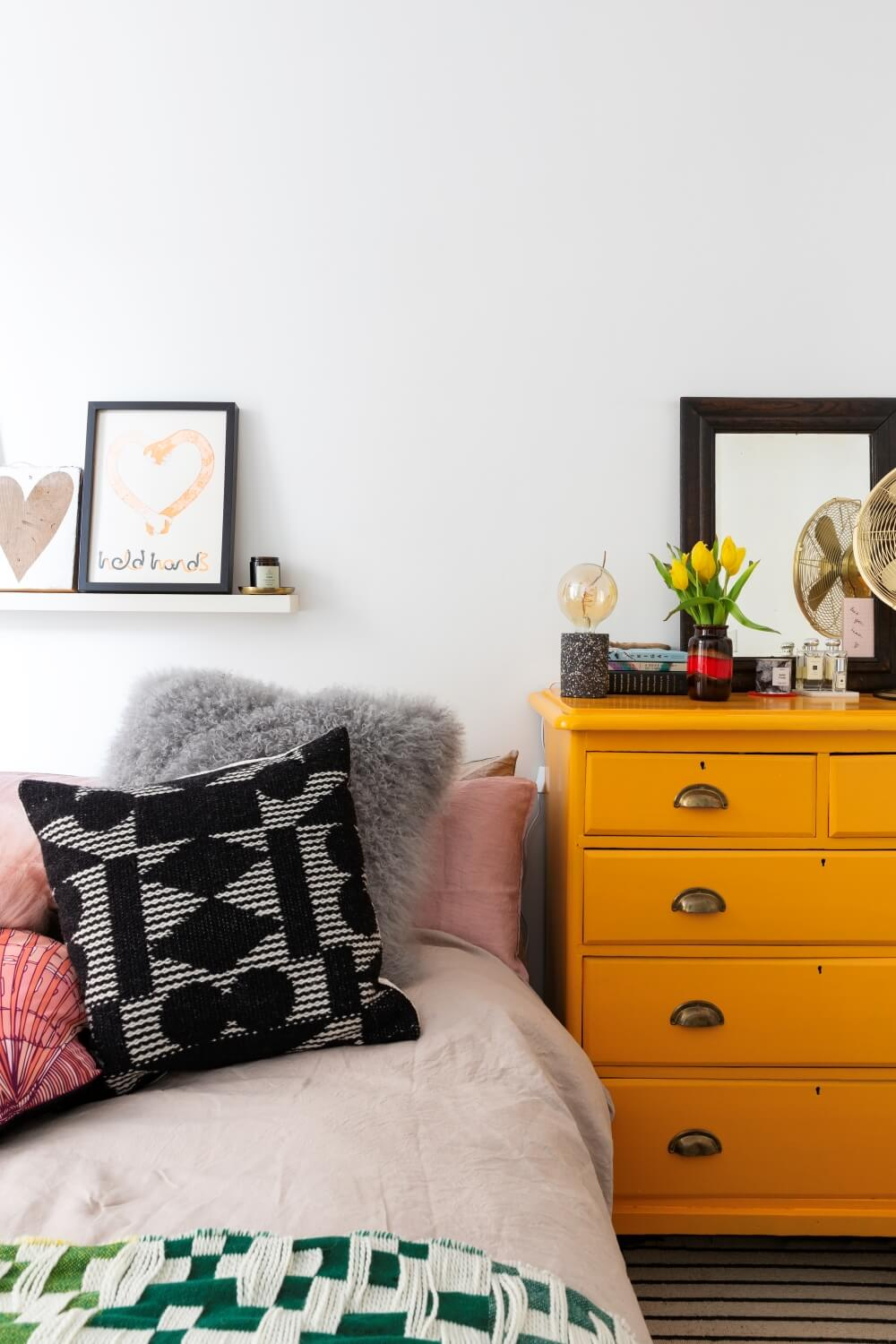 Painted yellow chest of drawers next to bed in the bedroom