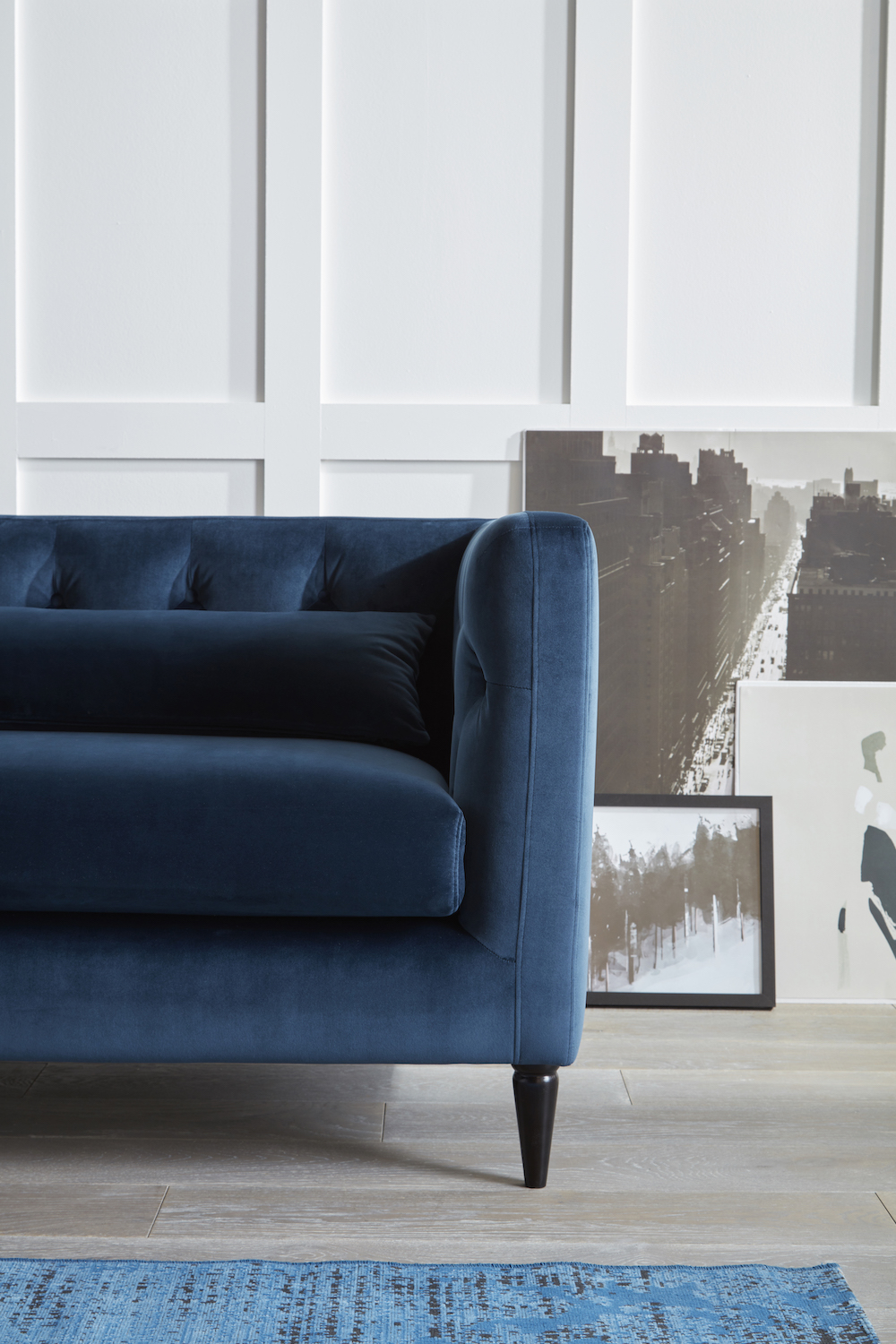 Right side view of the blue MYA sofa pictured against a white paneled wall / grillo designs