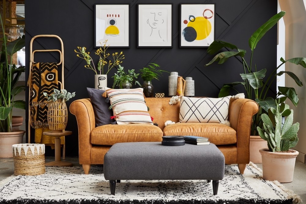 Styled space created by medina grillo using the leather look so simple ola sofa. Sofa is against a black panelled feature wall with abstract art.