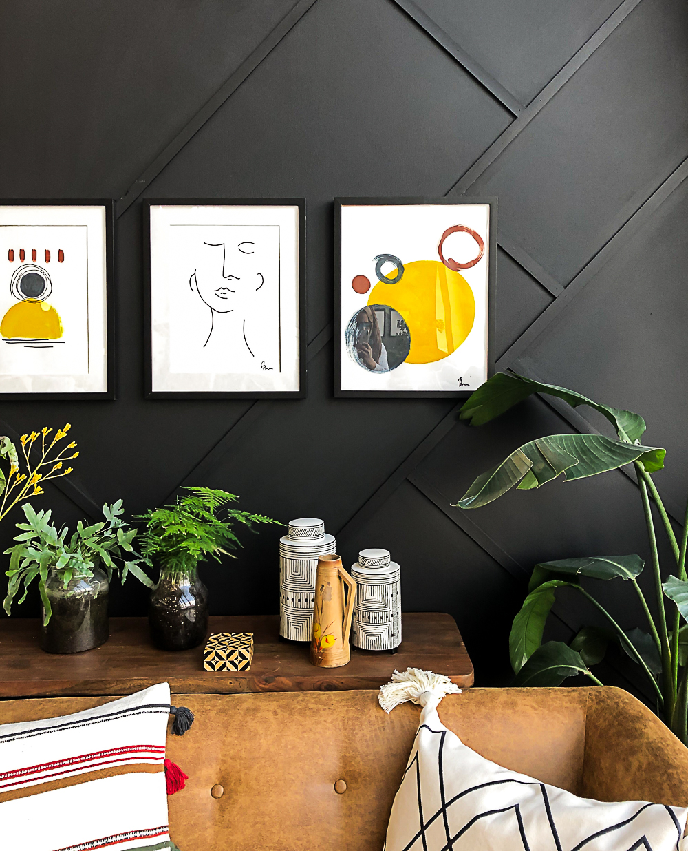Close up image of 3 abstract framed images on the geometric paneled black wall / grillo designs