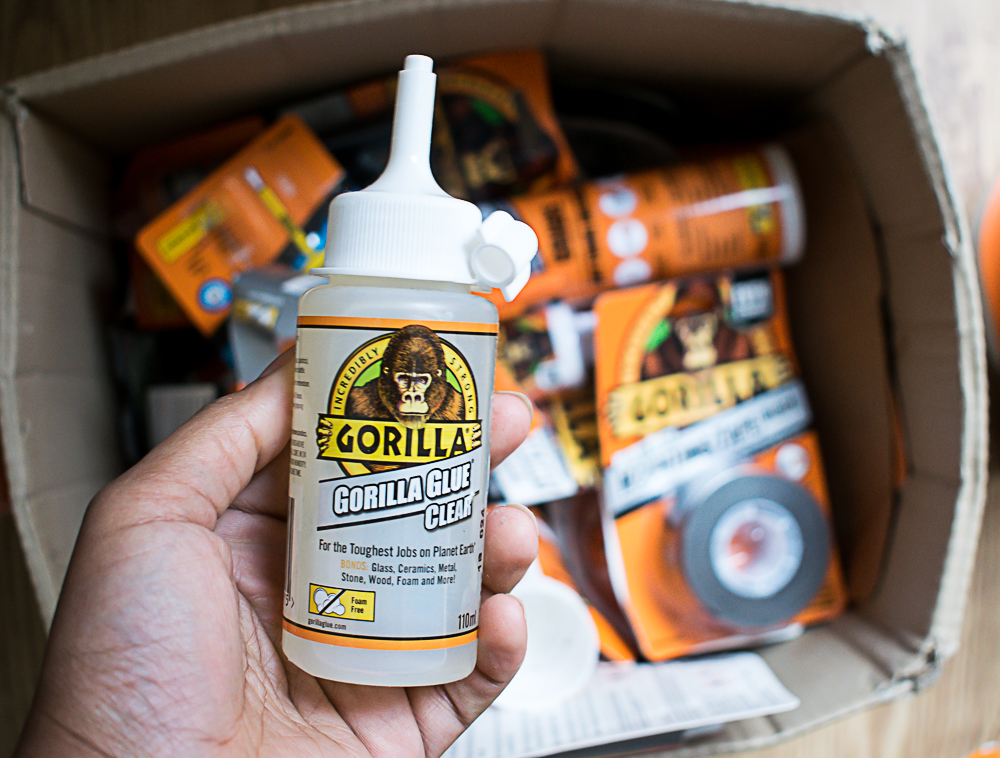 My hands holding up the gorilla clear glue over a box of gorilla glue products