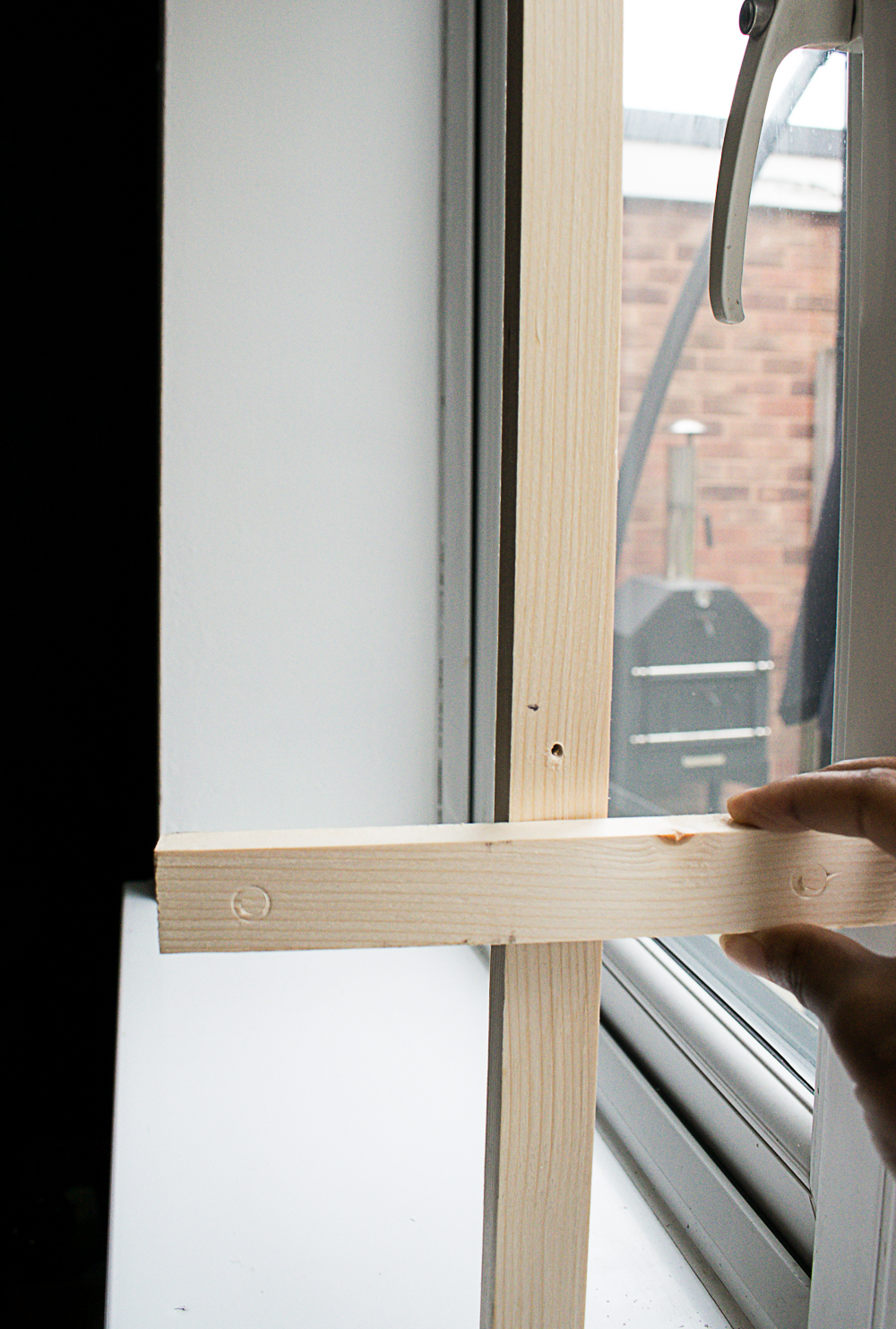 Showing wear to position the wooden brackets on the vertical frame in the window