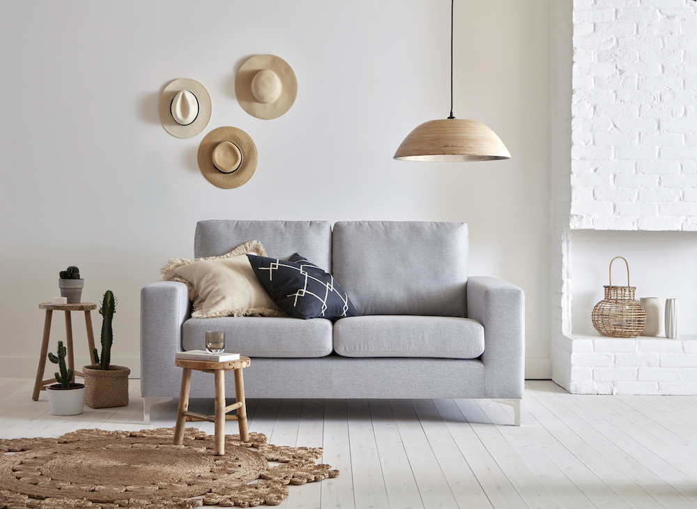 The max sofa in grey fabric pictured under a pendant lamp and a gallery wall of three straw hats