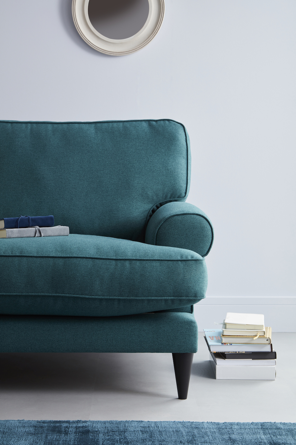 Right side view of the viv sofa in a teal fabric pictured next to a pile of books