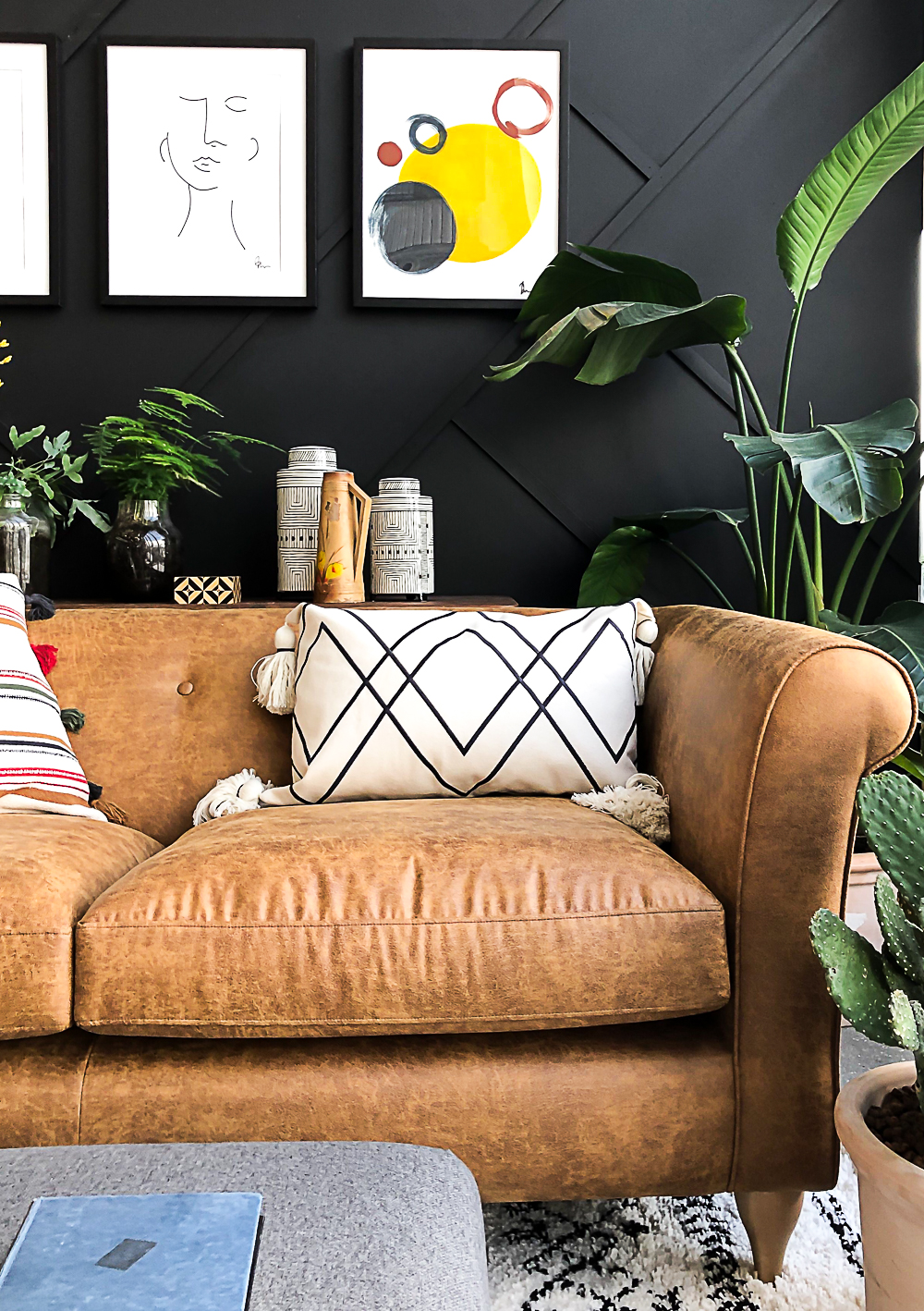 Image of the right side of the leather look ola sofa next to large green plants. Sofa is pictured against a geometric paneled black wall