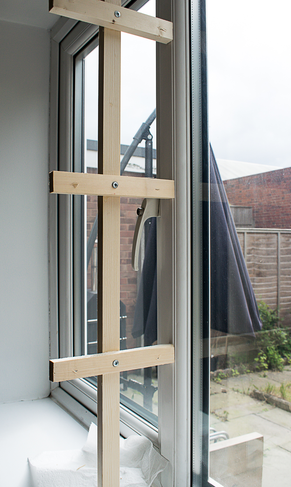 Final image of the unpainted wooden frame in the middle of the window with three of the brackets screwed across the frame