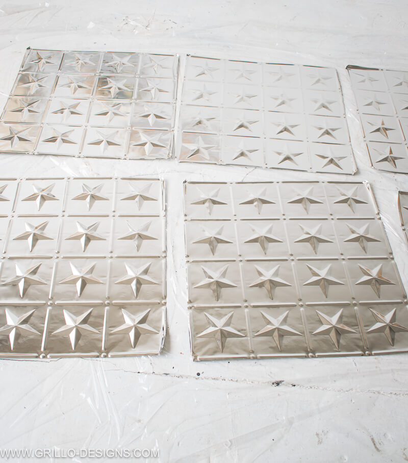 4 x metallic tin tiles placed on plastic sheeting about to be painted
