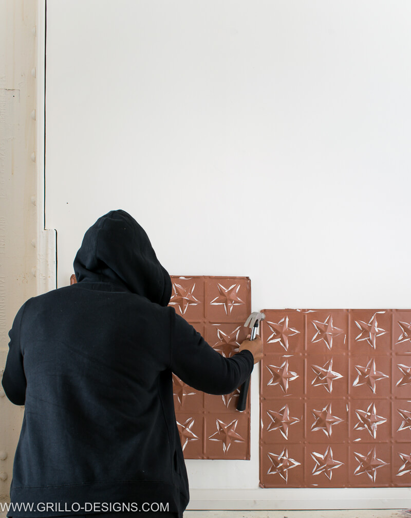 image of me Securing the tin tiles to the wall with a nail and hammer /