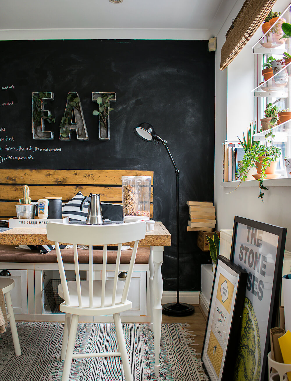 The window in the dining space. A cork board table with white chairs against a chalkboard wall seen