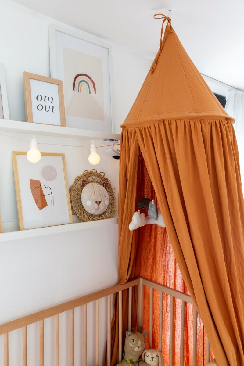 White picture ledges with nursery artwork over a crib. A terra cotta colored canopy surrounds the bed.