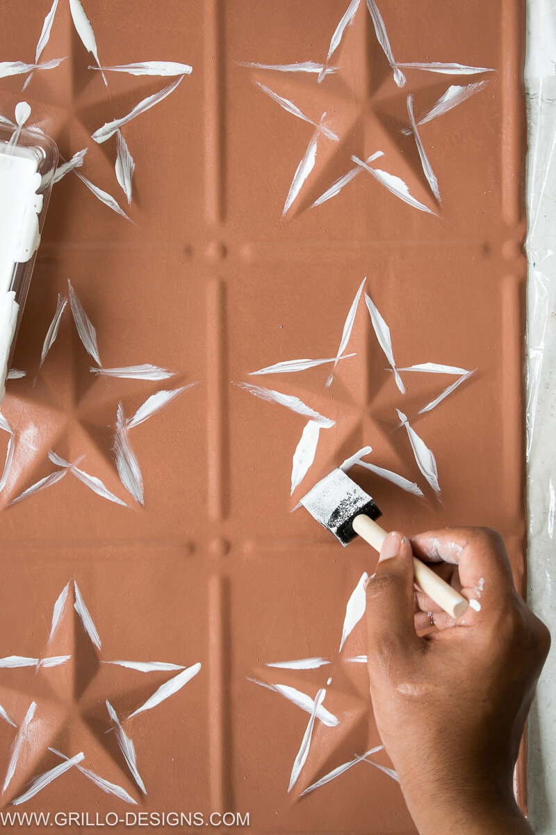 Image of paint being applied to the outlines of the pressed stars on the tin tiles